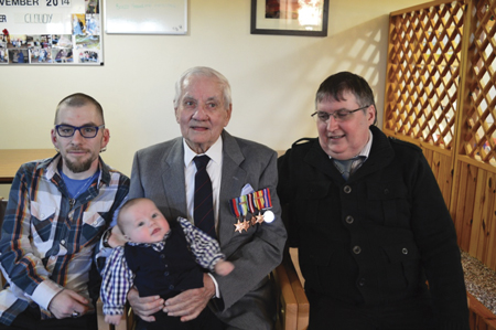 Four generations… Alexander Campbell, with his five medals, is pictured with son Malcolm Neil, grandson Neil and great grandson Alex Neil